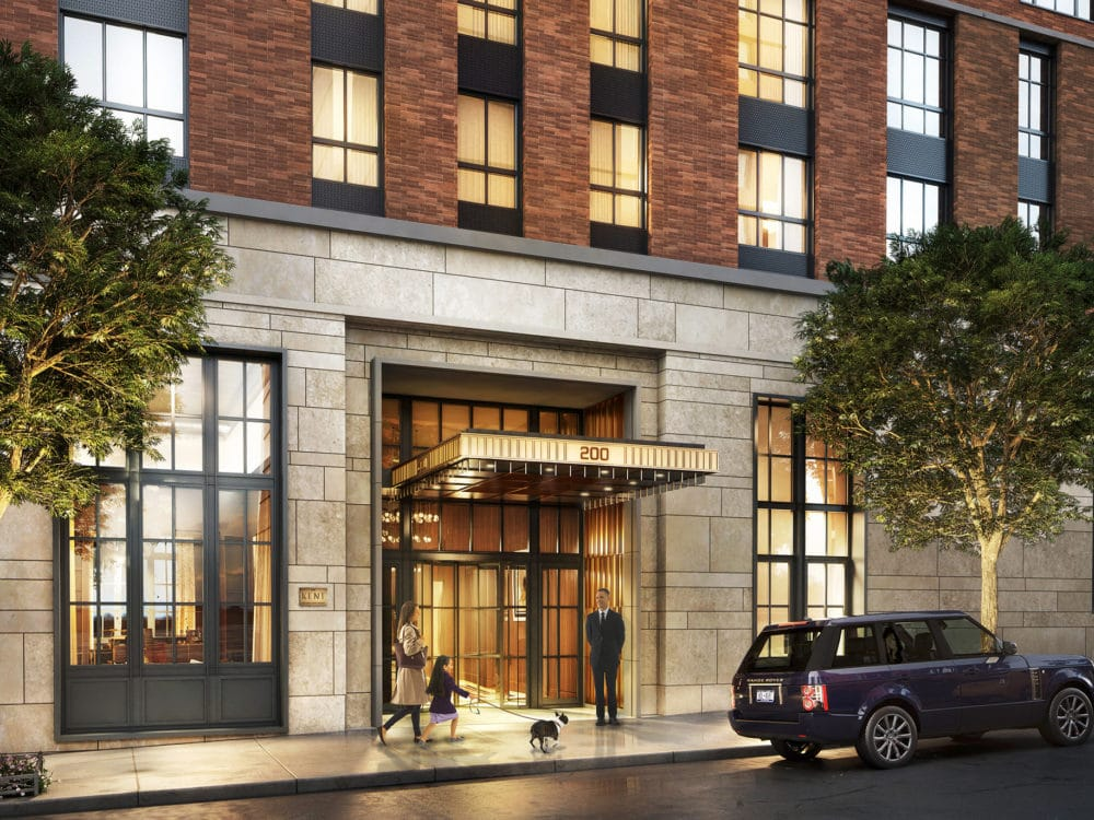 Exterior view of entrance to The Kent Condos in New York. Stone to brick exterior walls, double doors with canopy & doorman.
