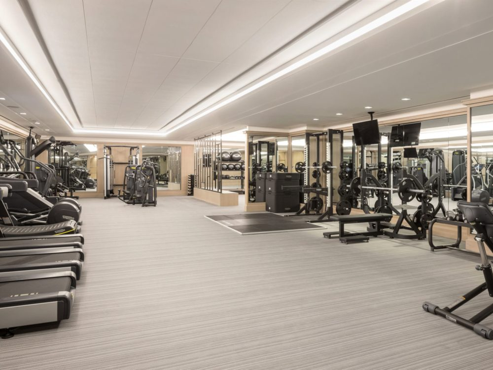 Fitness center at The Kent luxury condos in New York. Mirrored walls & carpet floors with free weights and cardio equipment.