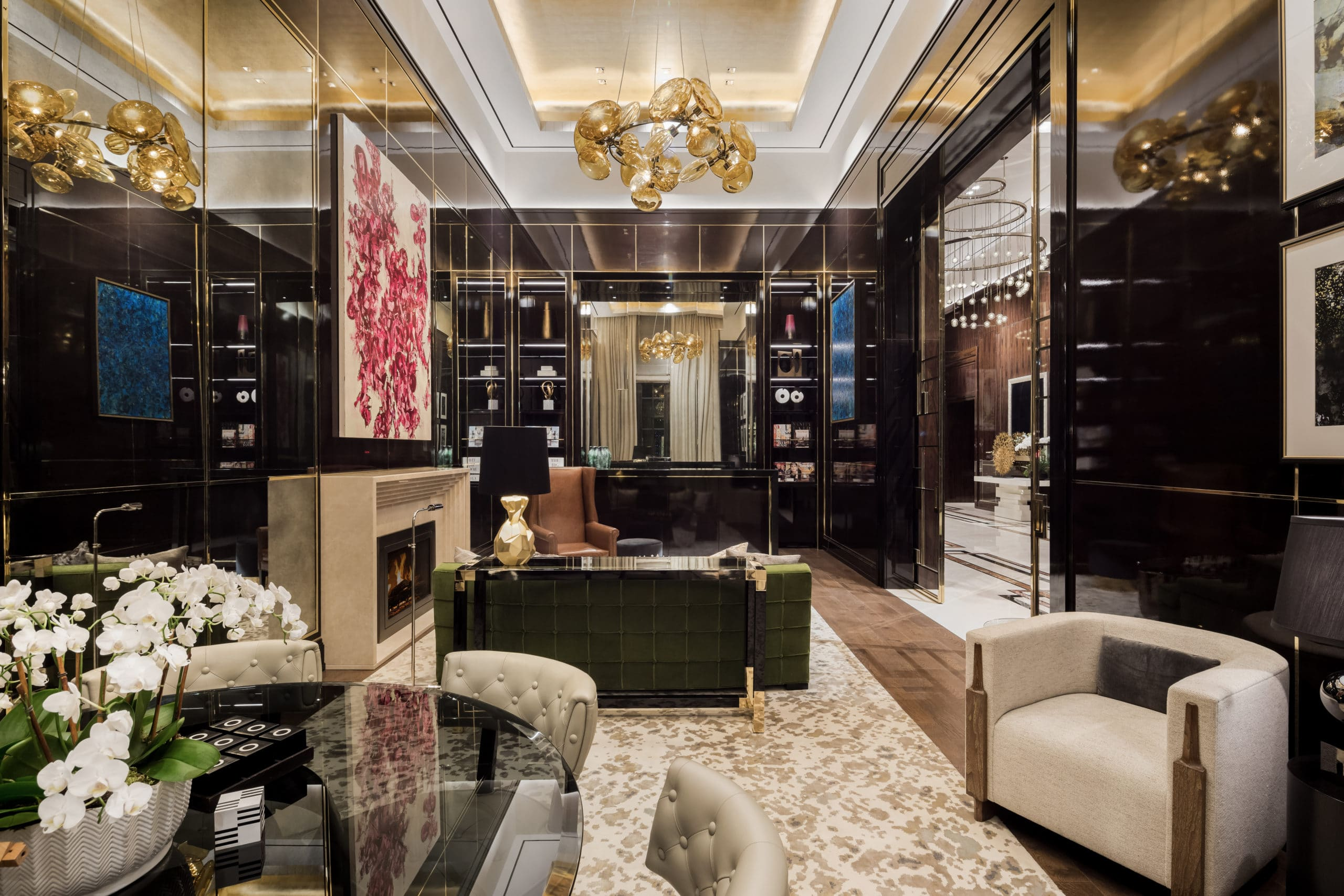 The Kent luxury condominiums in New York City. A room with black walls, built in shelves, and seating by a fireplace.