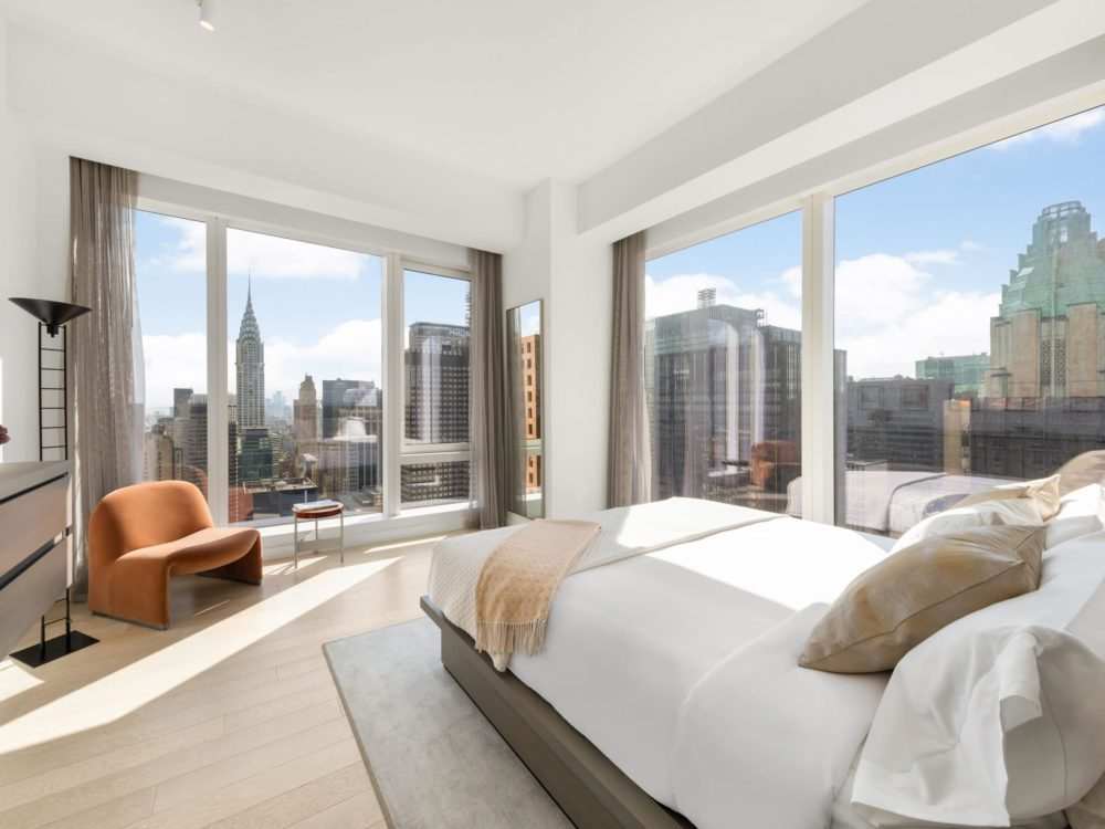 Bedroom at The Centrale condos in New York City. Corner bedroom with a bed, dresser, and large windows with city views.