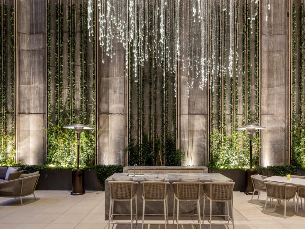 Outdoor space for residents at The Centrale in NYC. Hanging glass art chandelier above seating area and bordering planters.
