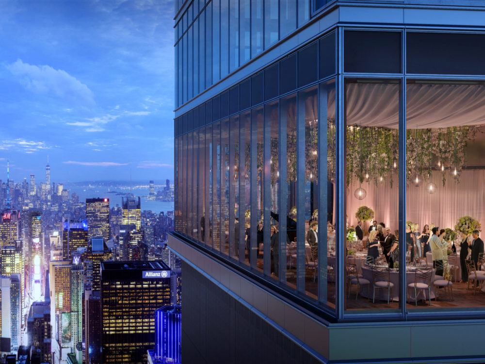 Exterior view of Central Park Tower looking into residence living room. Includes view of New York City during night fall.
