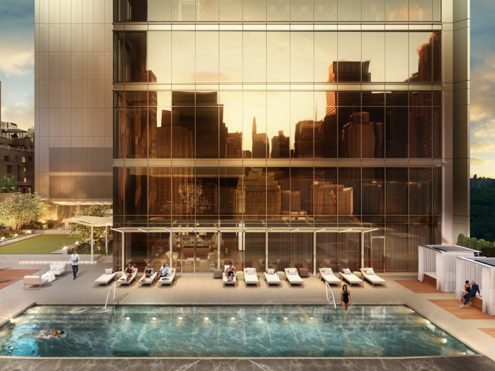 Exterior view of Central Park Tower residence outdoor pool with view of NYC. Has lounge chairs and reflective windows.