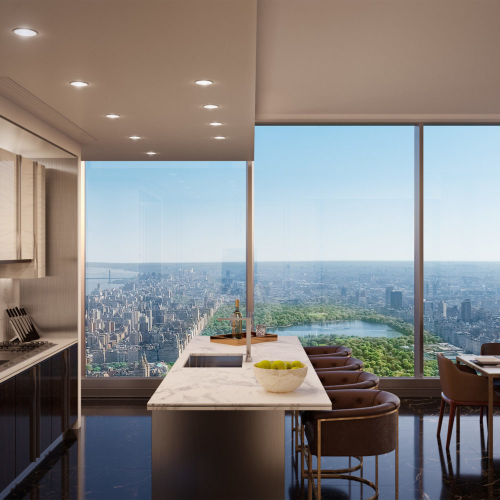 Interior view of Central Park Tower residence kitchen with window view of NYC and Central Park. Has white island counter.
