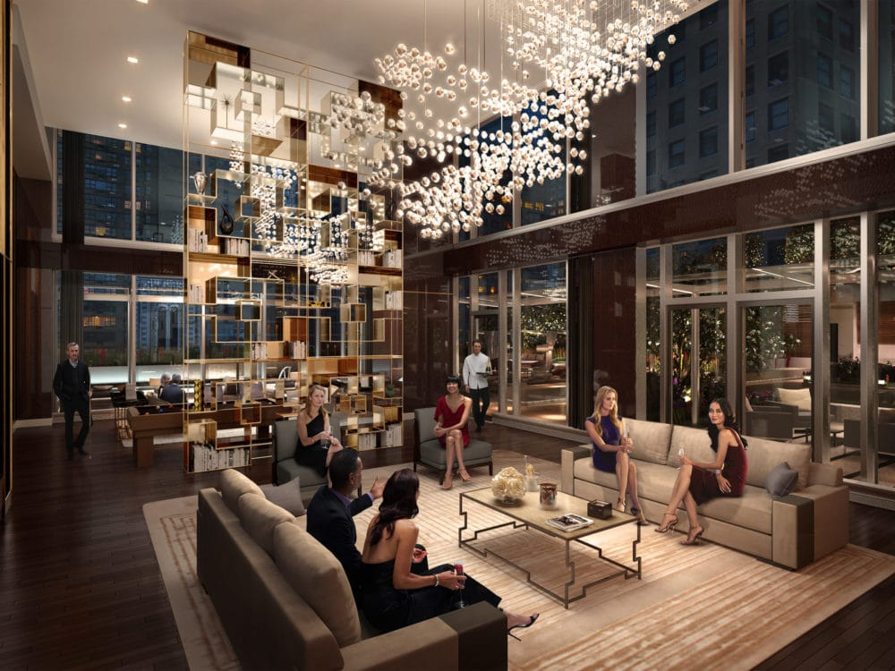 Interior view of Central Park Tower residence lobby in NYC. Has wooden panels, glowing chandelier, and lounging furniture.