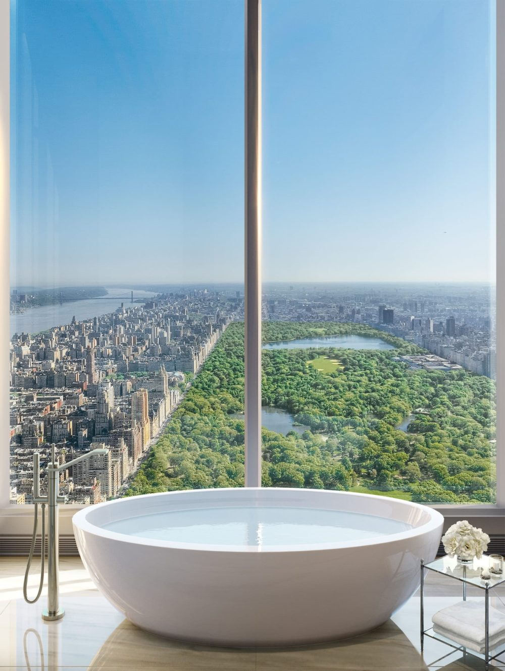 Interior view of Central Park Tower residence bathroom with window view of New York City and Central Park.