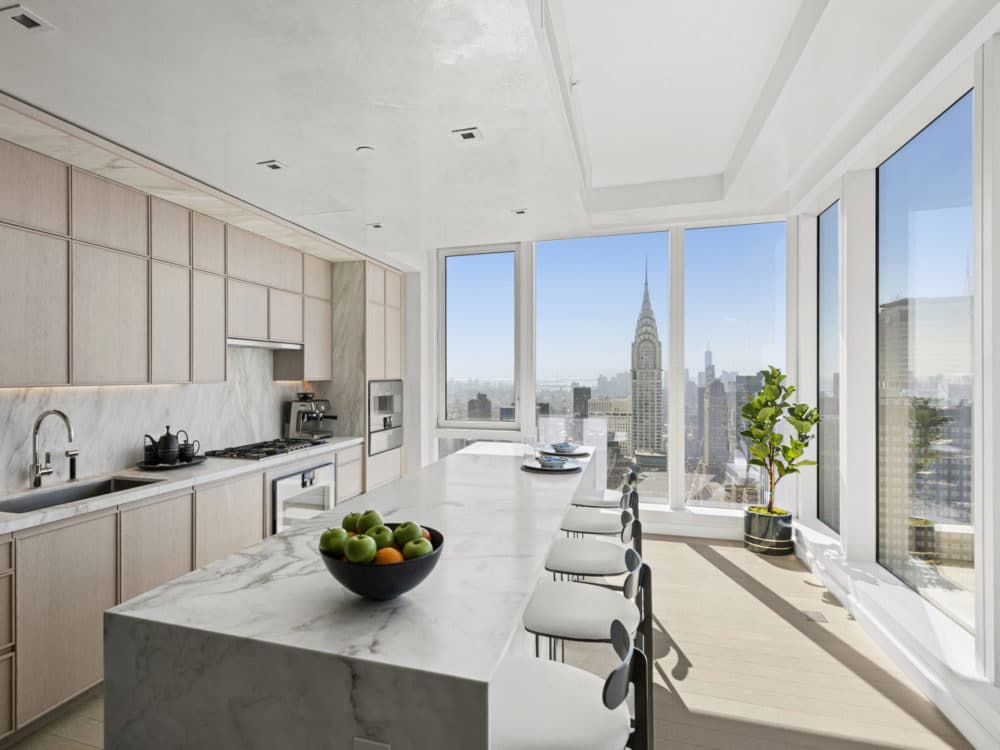 Kitchen in The Centrale condos in NYC. Tan cabinets, white marble countertops, a long island and chairs with city views.