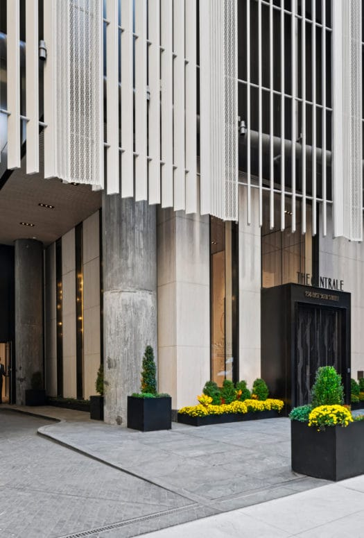 Entrance to The Centrale condos in NYC. Driveway running between buildings with potted shrubs and a doorman at the entrance.