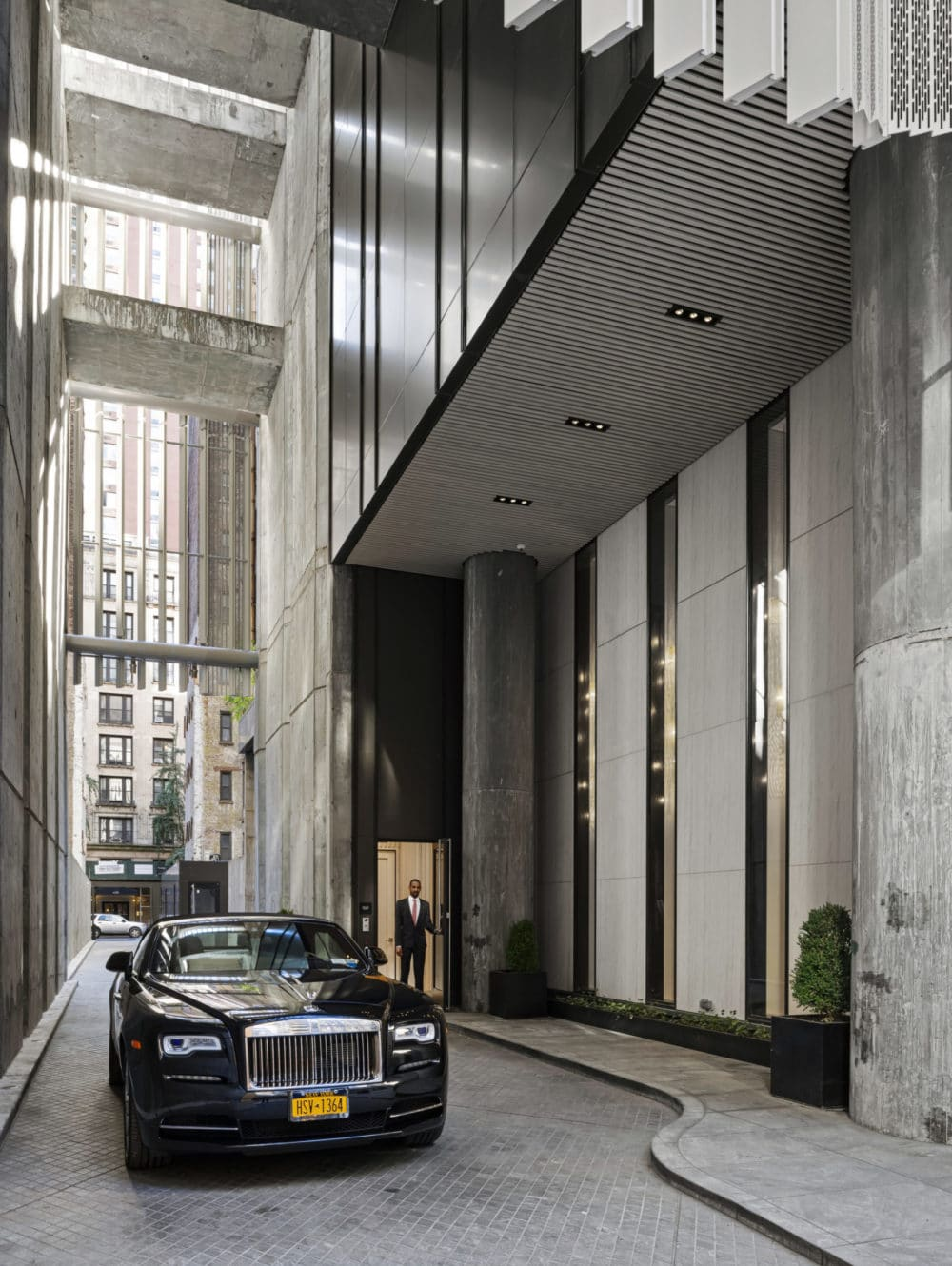 Valet parking at The Centrale luxury condos in New York. Car parked in the driveway next to building with a doorman waiting.