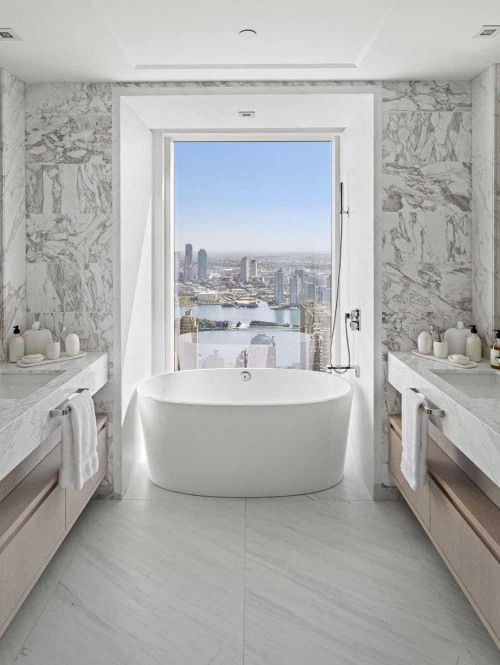 Bathroom at The Centrale in New York. Condo bathroom with double vanities and large soaking tub overlooking Manhattan.
