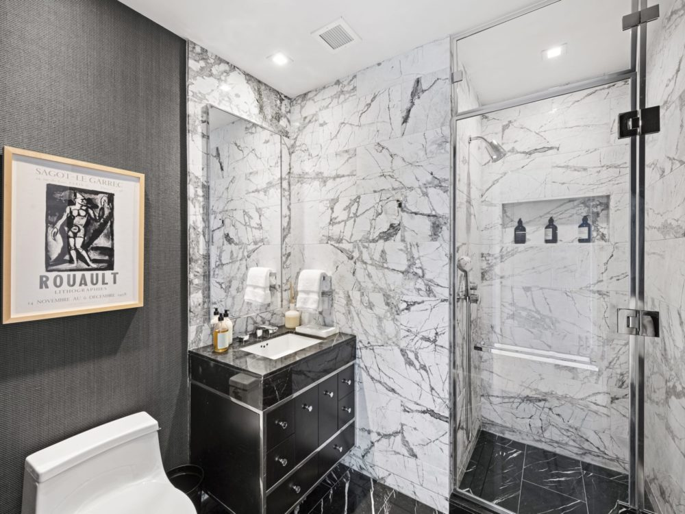 A condo bathroom with white marble shower, a vanity with mirror, and dark gray wall with a picture at The Centrale in NYC.