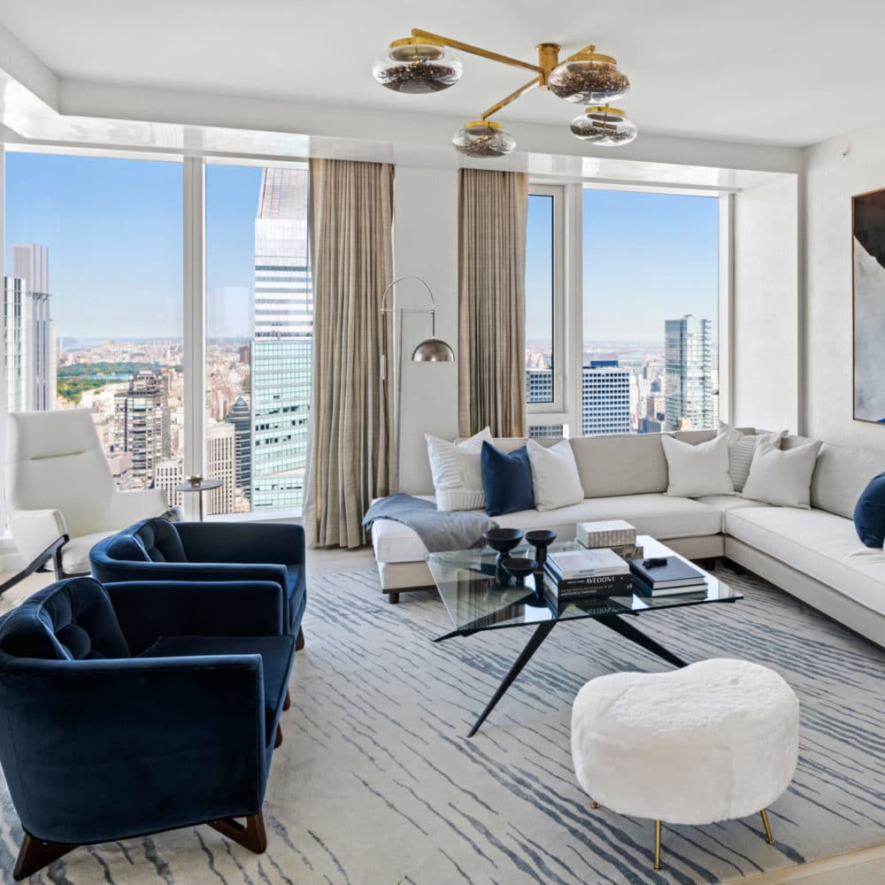 Corner living room with floor-to-ceiling windows, blue chairs, and a white couch overlooking New York at The Centrale condos.