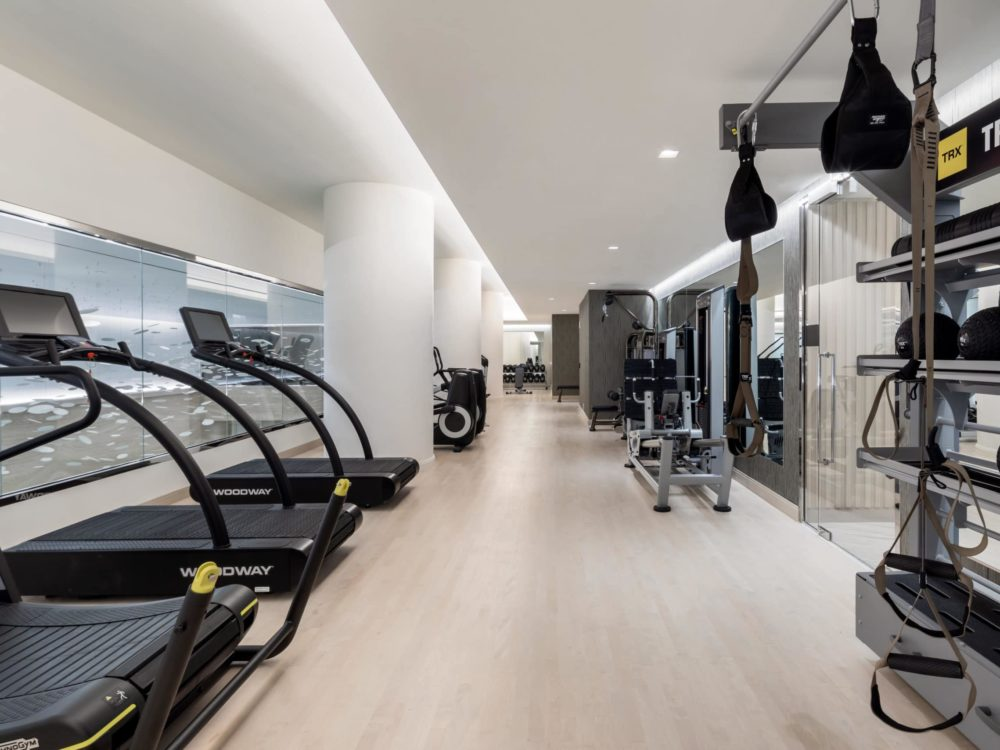 Fitness center at The Centrale condominiums in New York. Long room with workout equipment, treadmills, and view of the pool.