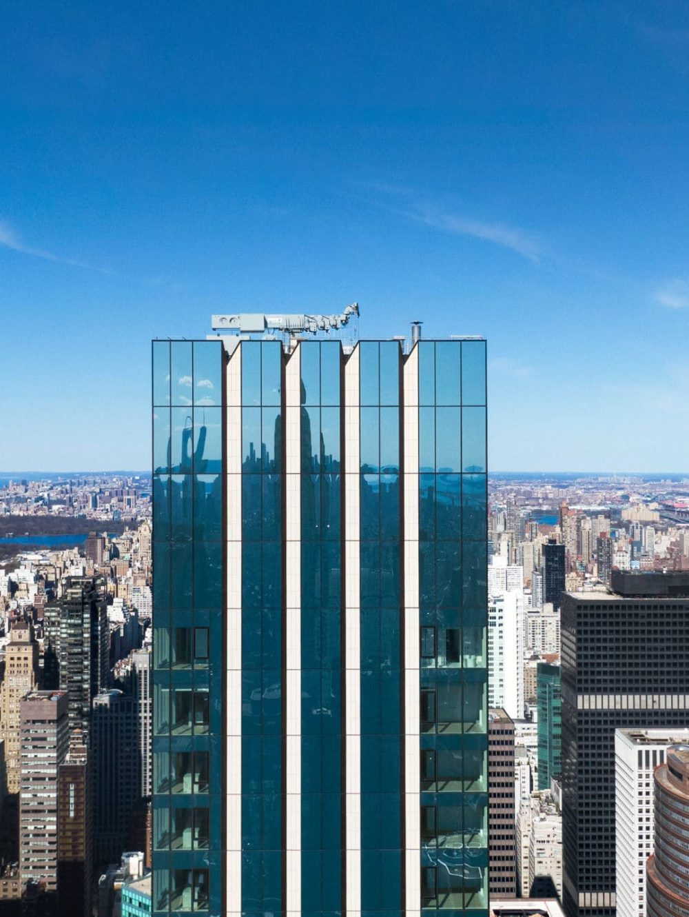 Birdseye view of The Centrale condos in New York. Tower with glass facade in downtown with buildings and blue sky behind it.