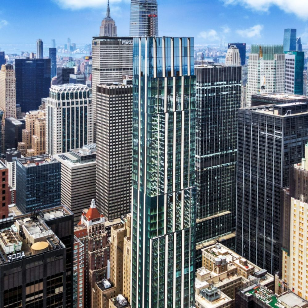 Aerial view of The Centrale residences in NYC. Multiple high rises & tall buildings in downtown with daytime blue skies.