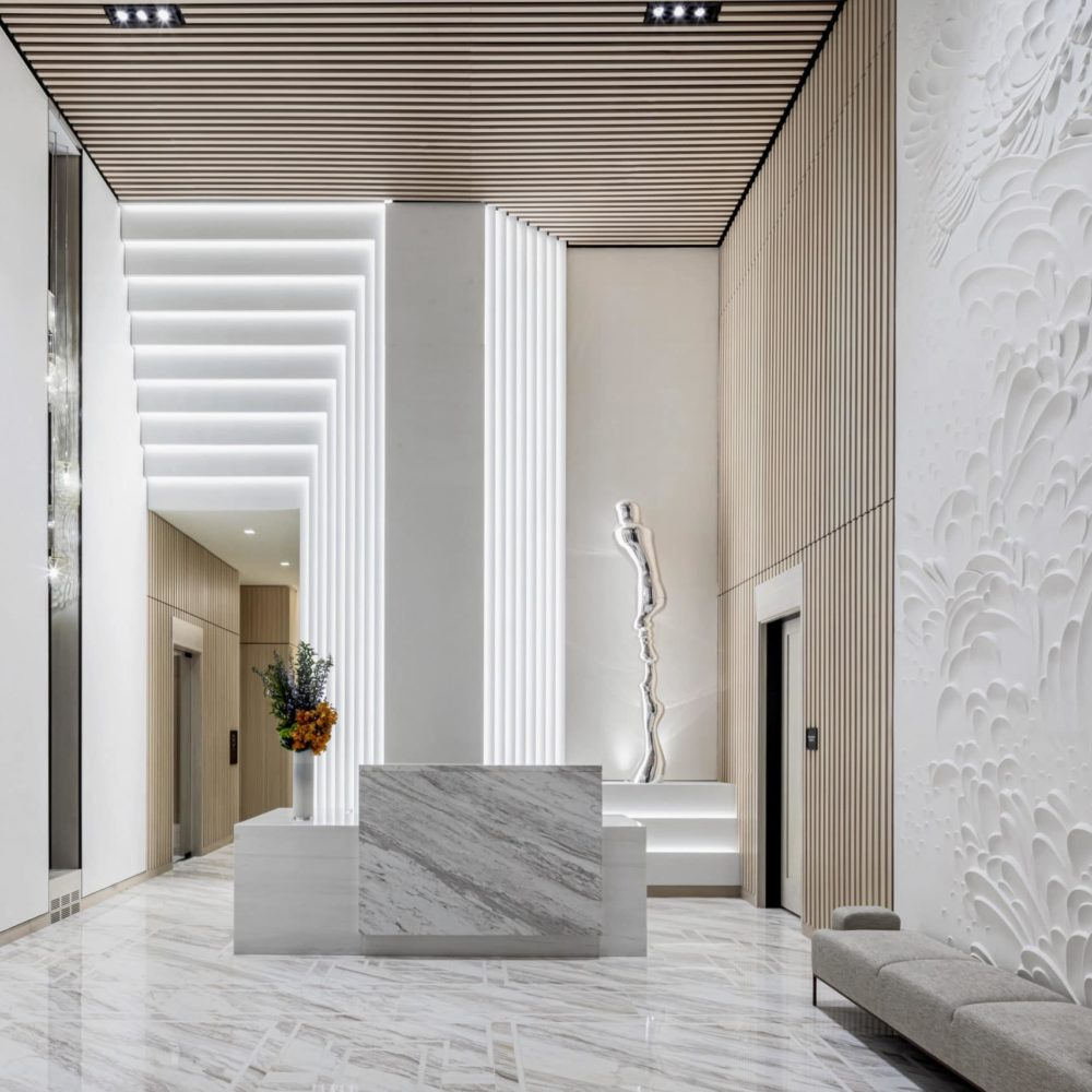 Lobby at The Centrale luxury condos in New York. White walls, marble floors, and high ceilings with elevators in the distance.