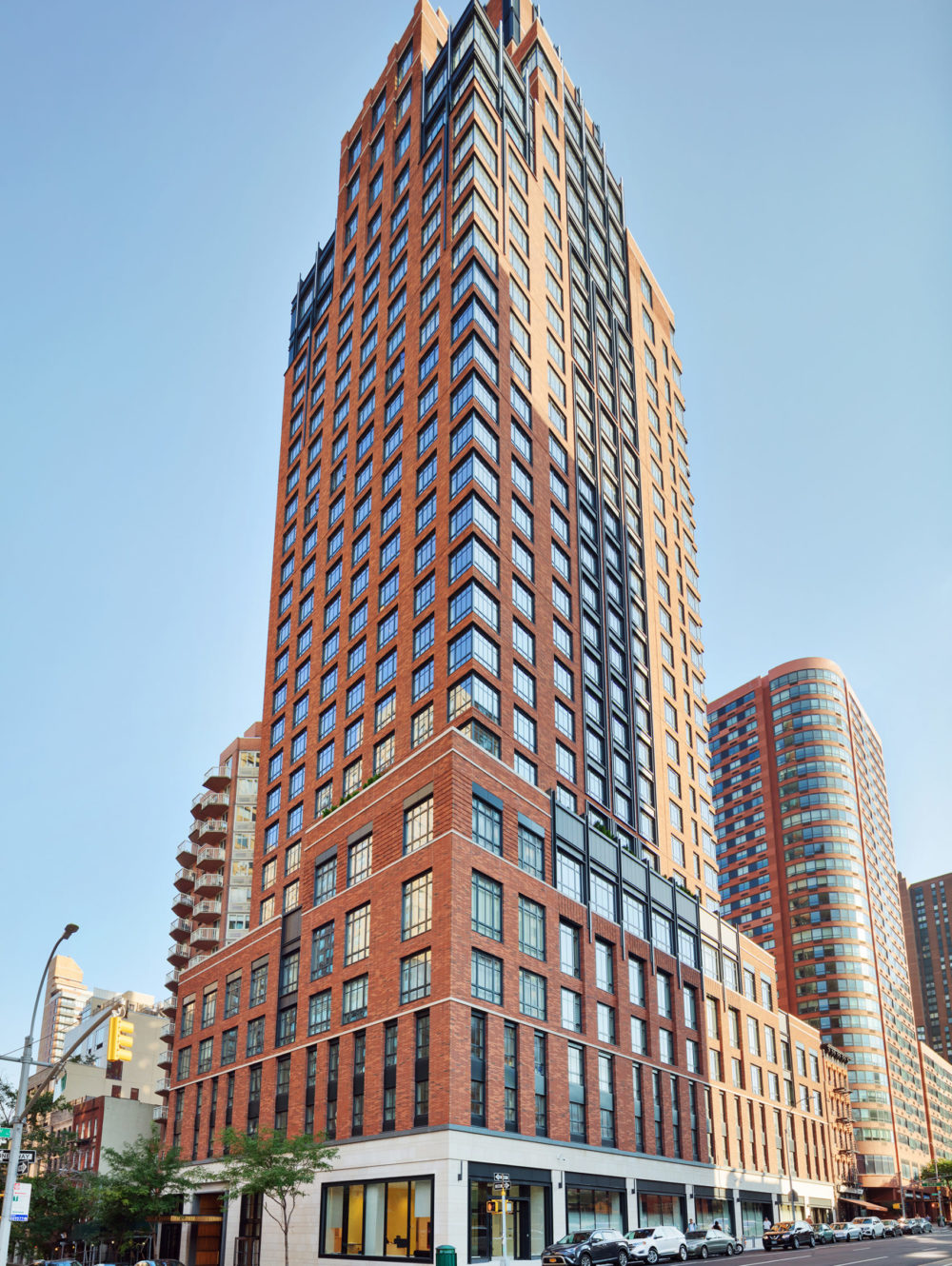 Exterior view of The Kent condominiums in New York. Street level view looking up at the brick high rise during daytime.