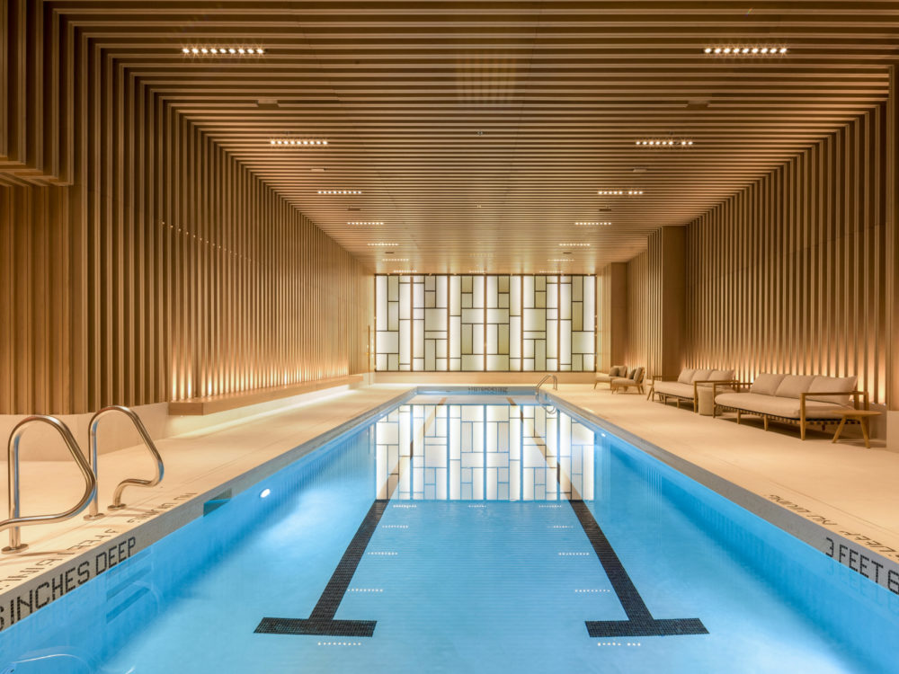 55 ft pool inside The Kent condos in New York City. Long lap pool with wood walls, raised ceiling and sauna access.