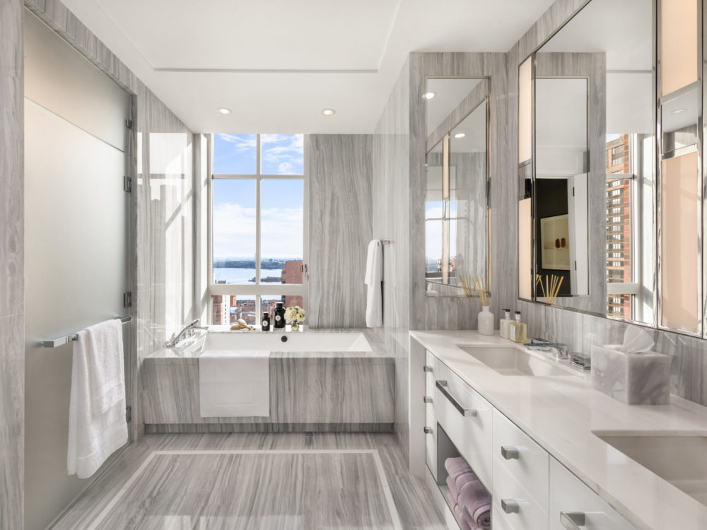 Master bathroom in The Kent condos in NYC. Ivory stone walls, countertops and accents with double vanity and soaking tub.