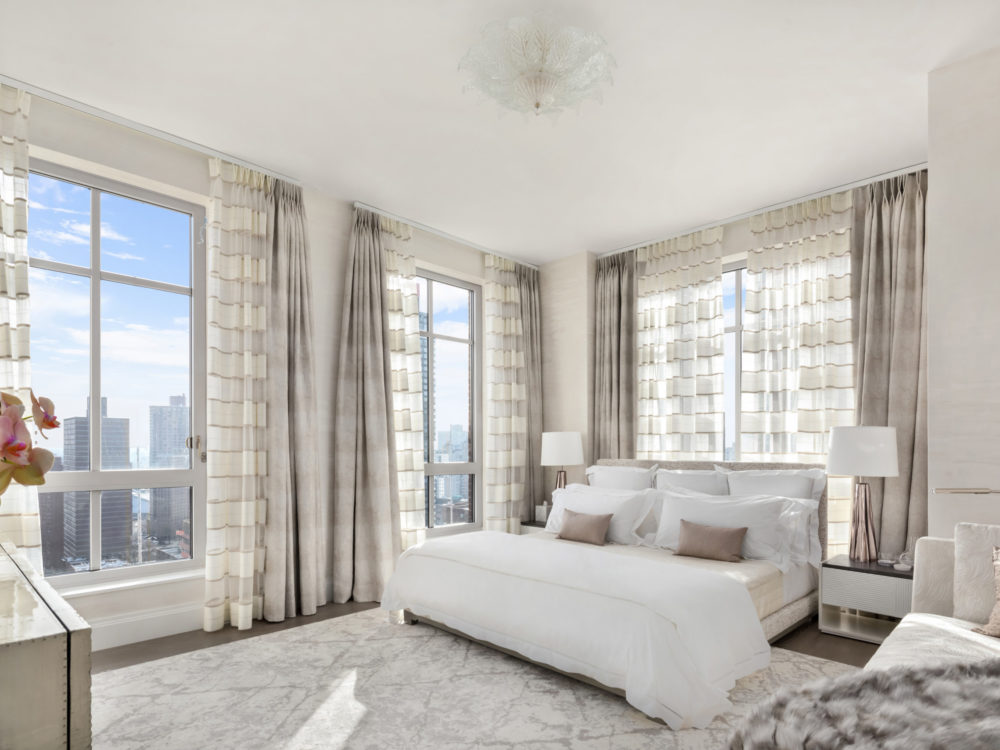 Master bedroom at The Kent condos in NYC. Large bedroom with white walls & finishes, a bed, and large windows with views.