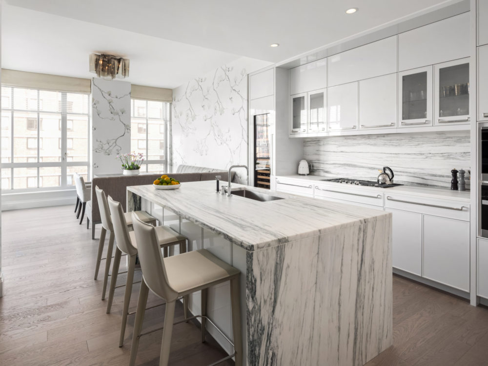 Kitchen in The Kent condominiums in New York. White walls and cabinets, stone countertops and center island with seating.