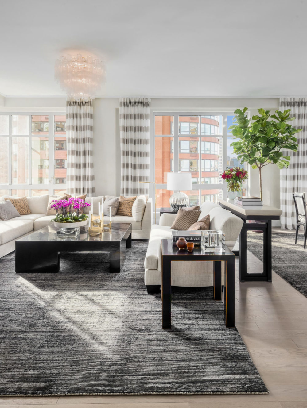 Living room in The Kent luxury condos in New York. Large open room with large windows, a large couch and black coffee table.