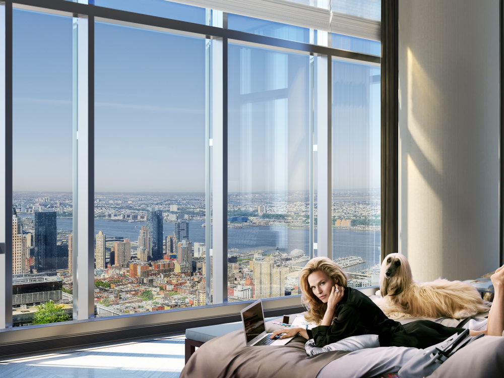 Interior view of Central Park Tower residence bedroom with window view of New York City. Has a woman laying on the bed.