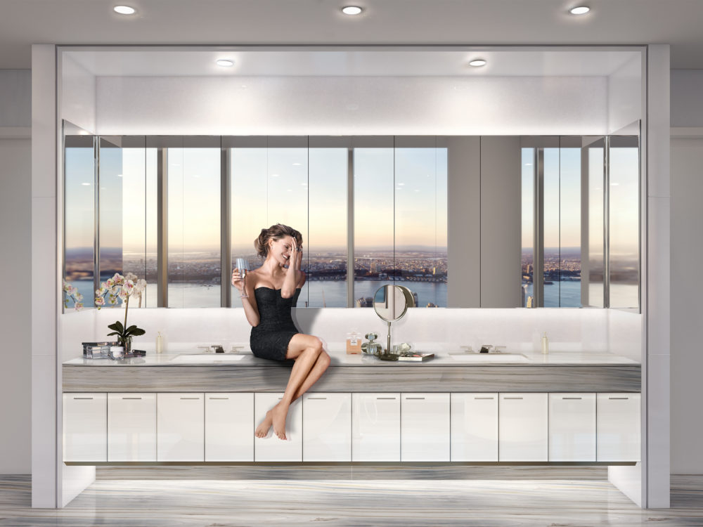 Interior view of Central Park Tower condominiums window view of New York City. Has a woman sitting on the counter.