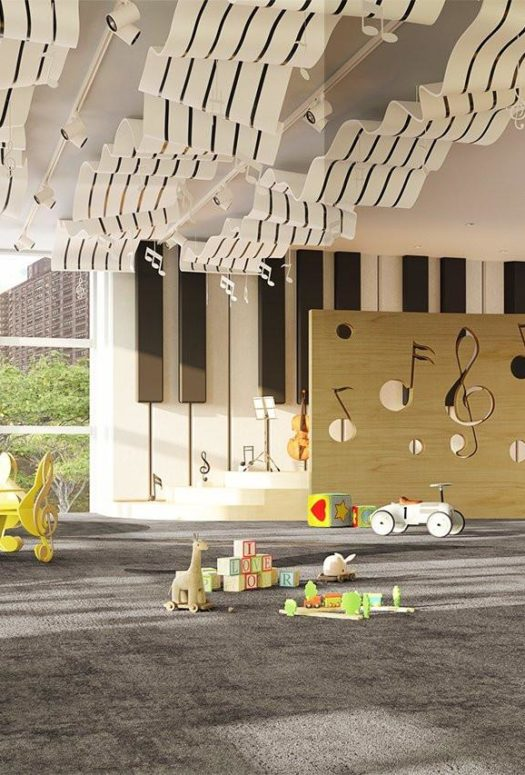 Interior view of playroom inside 200 Amsterdam condominium in NYC. Includes toys, red furniture, and sculpture ceiling.