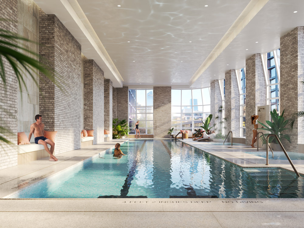 Interior view of Lantern House residence indoor pool in New York. Has lounging areas and bricked columns with glowing wall.