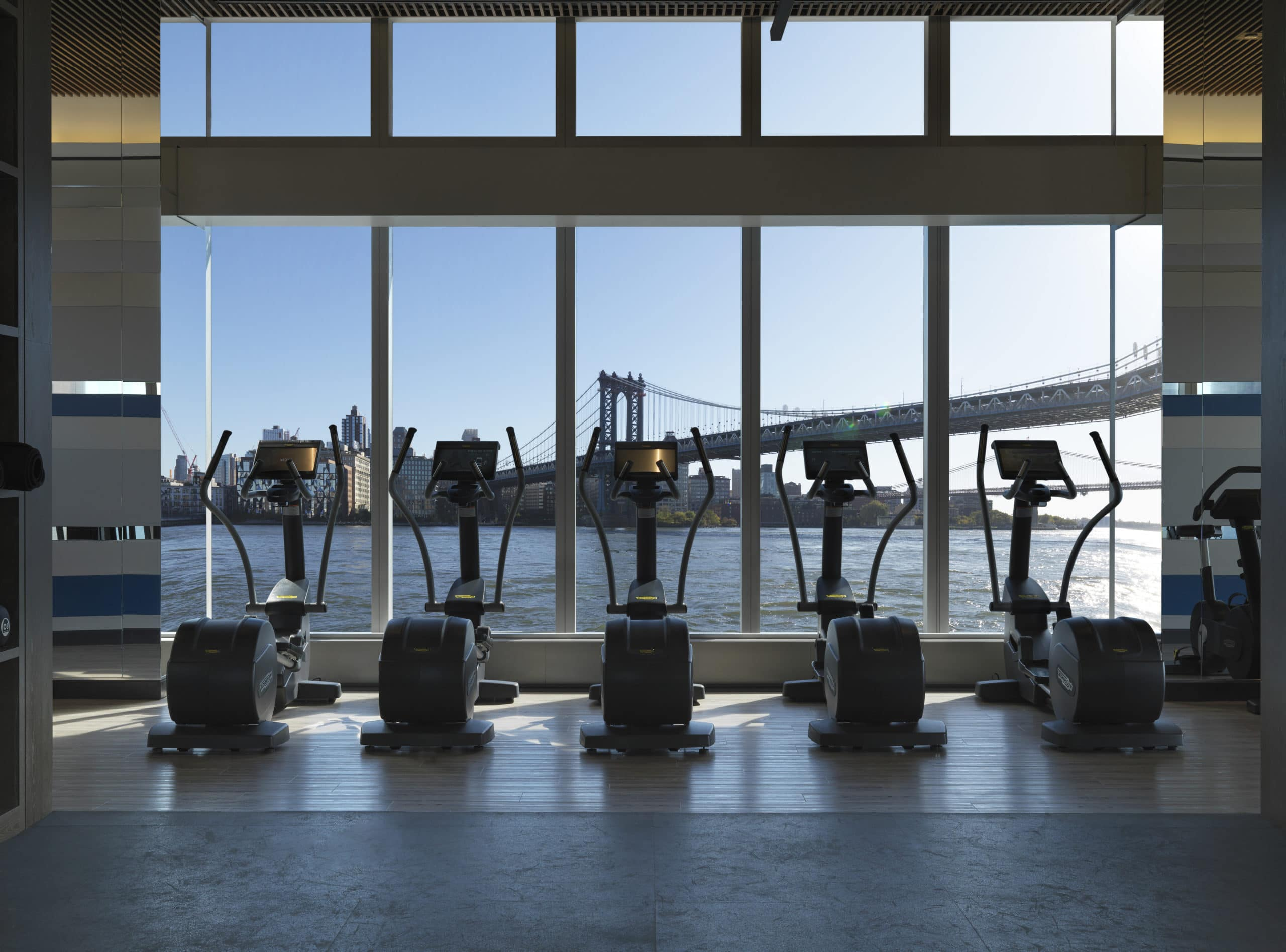Fitness center at One Manhattan Square condos in New York City. Cardio machines in front of tall windows with city views.