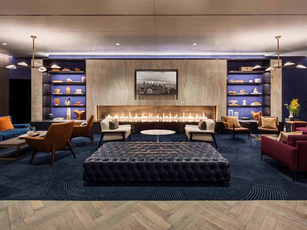 Resident's lounge at One Manhattan Square condos in NYC. Several seating areas, a long fireplace insert and two book shelves.
