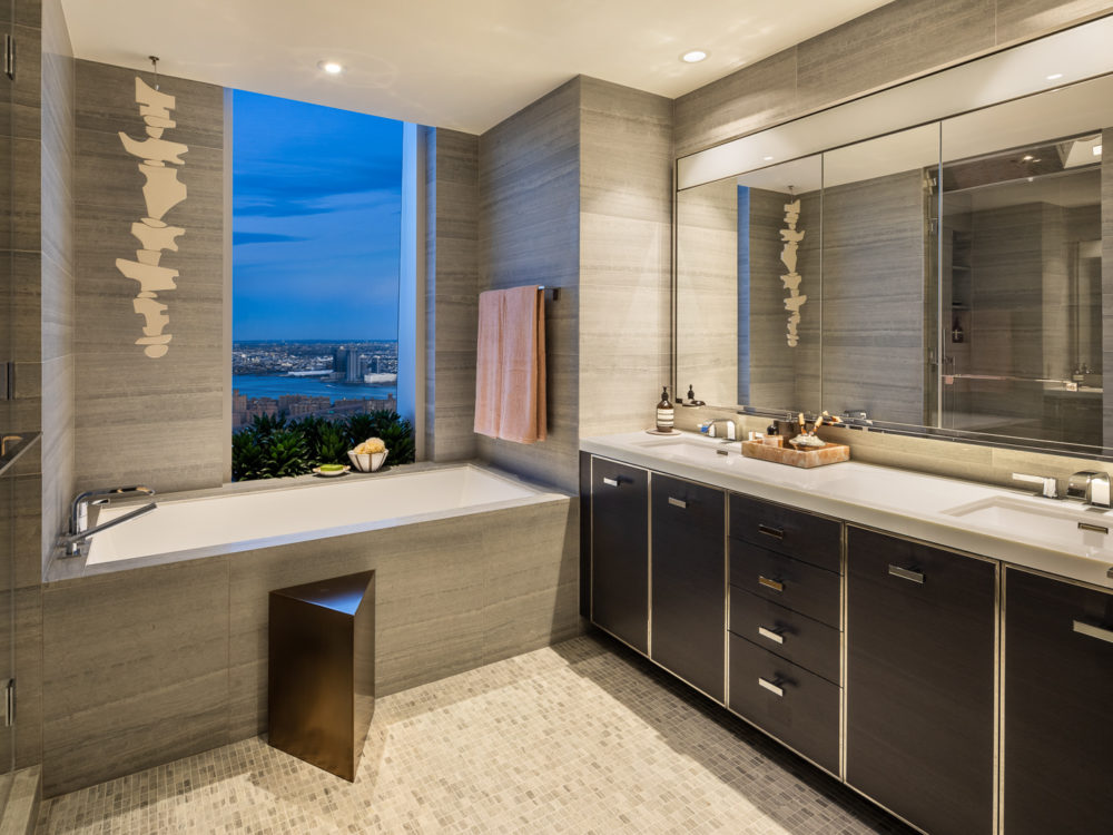 Bathroom at One Manhattan Square luxury condos in NYC. Dark double vanity with marble countertop, soaking tub and shower.
