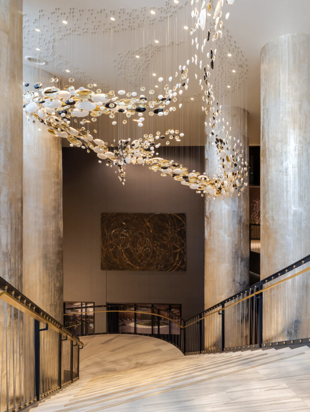 Top of oak staircase with chandelier and view of the elevators in One Manhattan Square luxury condominiums in New York City.
