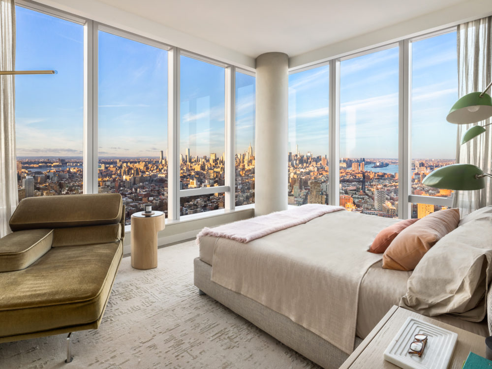 Corner condo bedroom at One Manhattan Square in New York. Bedroom furniture and floor-to-ceiling windows with city views.