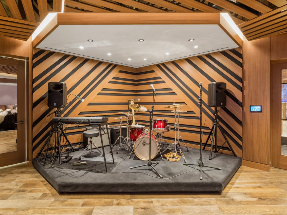 Music room at The Kent luxury condos in New York City. Small stage with instruments and wood backdrop with black lines.