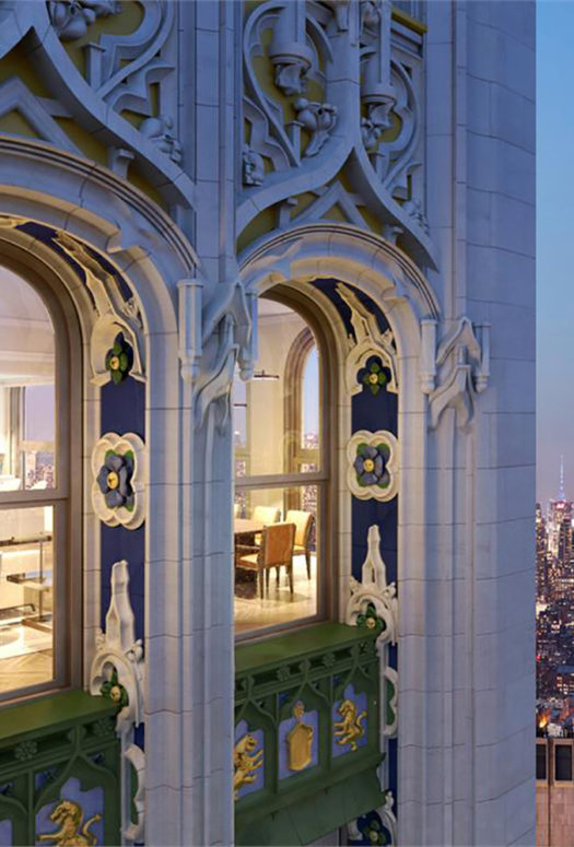 Exterior of the Woolworth Tower residences in New York. Gothic design and arched windows overlooking city skyline at night.