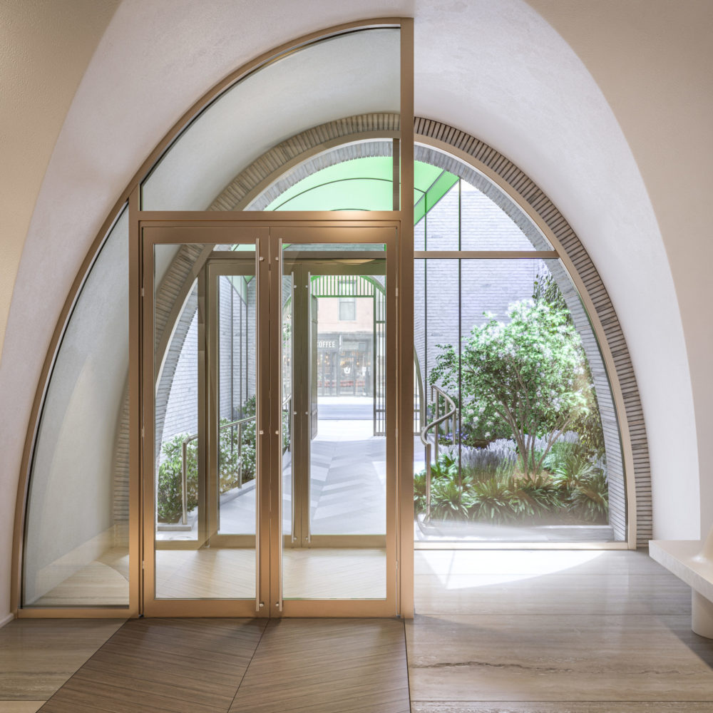 View of 180 E 88th street interior entry to condominiums in New York City. Has arched window panels and wood frame.