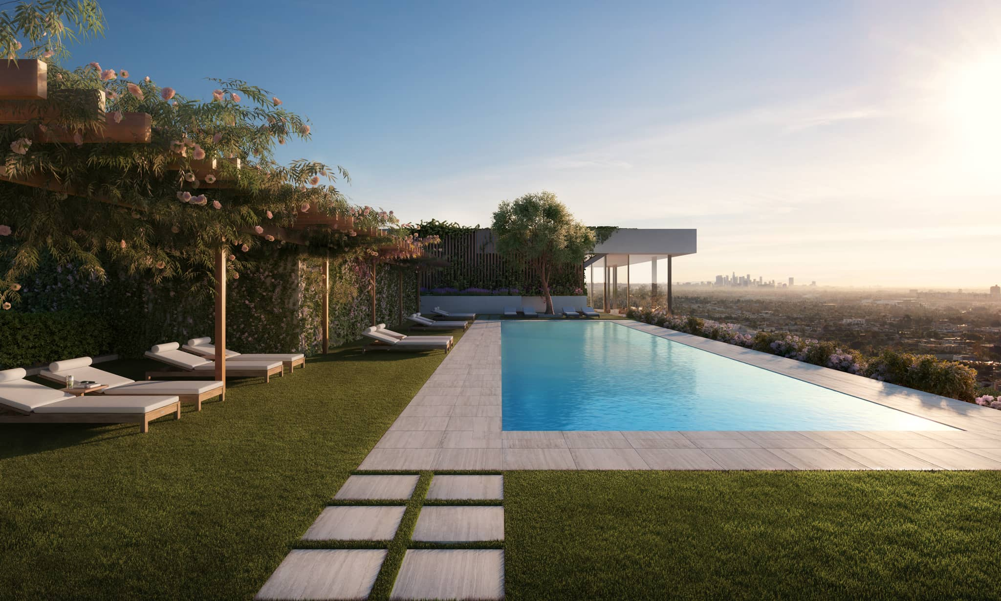 Double pool at West Hollywood residences with a sunset view overlooking Los Angeles. Includes fresh grass and lounge chairs.