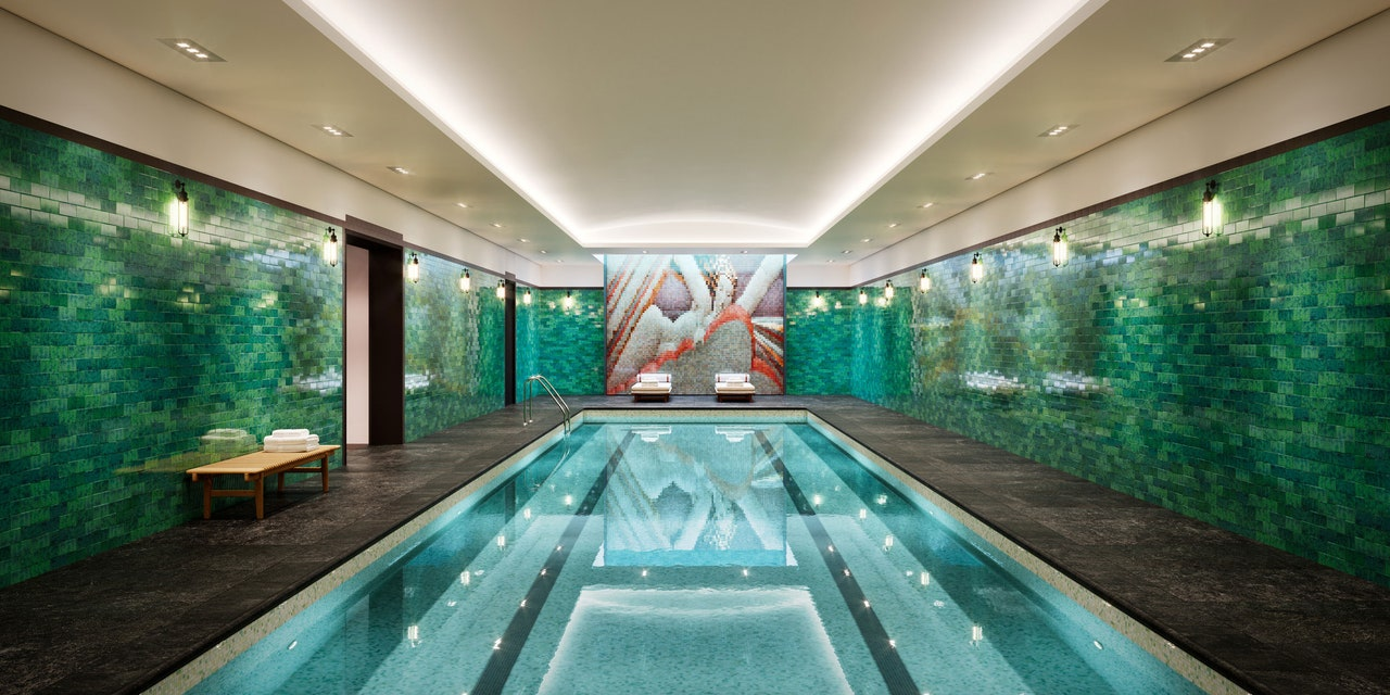 View of indoor pool at Rose Hill residences in New York City. Has dark green walls and dark brown flooring.