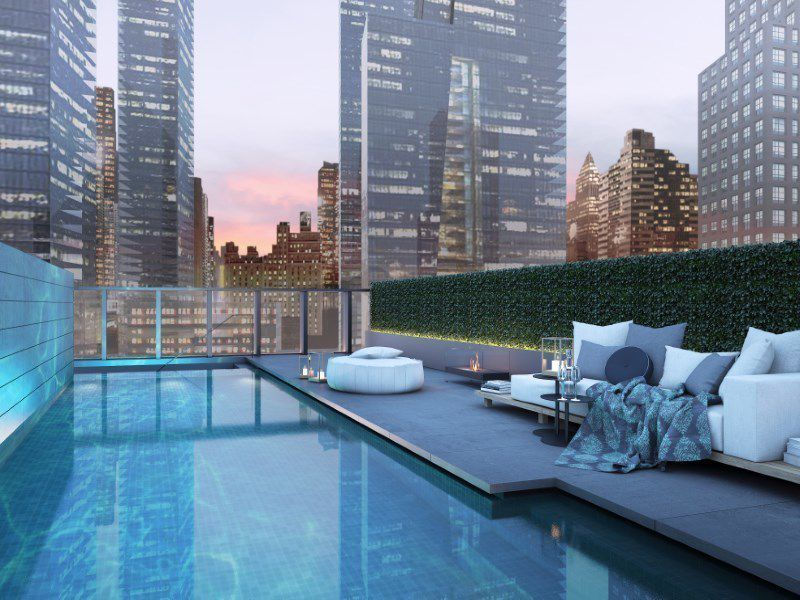 View of private outdoor pool at Soori Highline residences. Outward view of New York City with luxury sofa area.