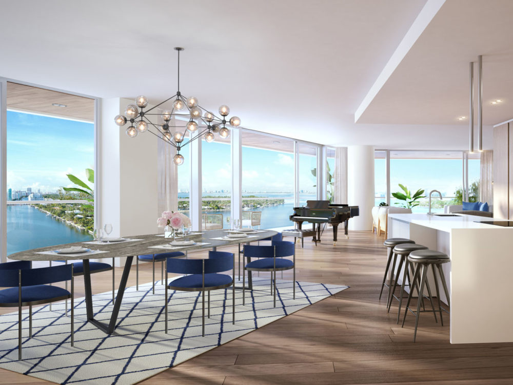 Interior view of Monaco Yacht Club residence kitchen and dining room. Has window view of the ocean and wooden floors.