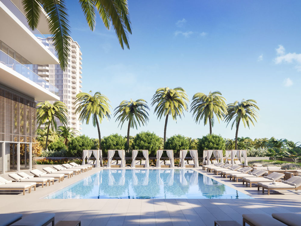 Exterior view of 2000 Ocean condominium with an ocean front pool with palm trees located in Hallandale Beach, Florida.
