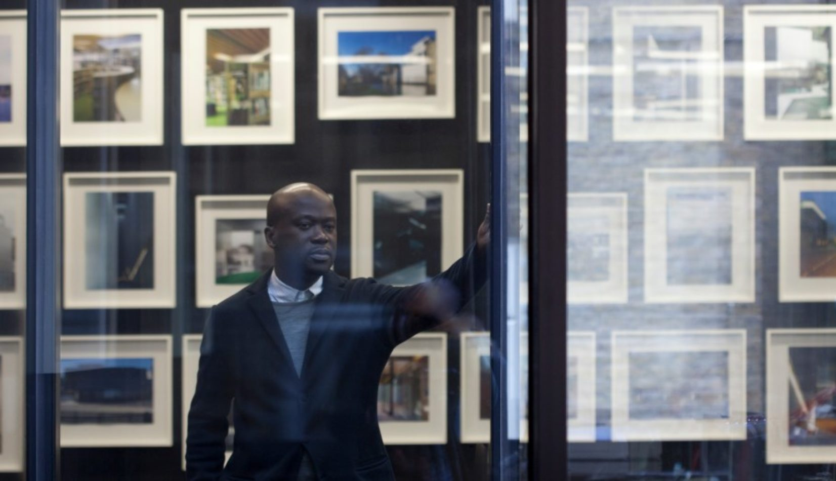 Portrait of David Adjaye looking out a window with his hand up on the wall. Framed pictures cover the walls behind him.