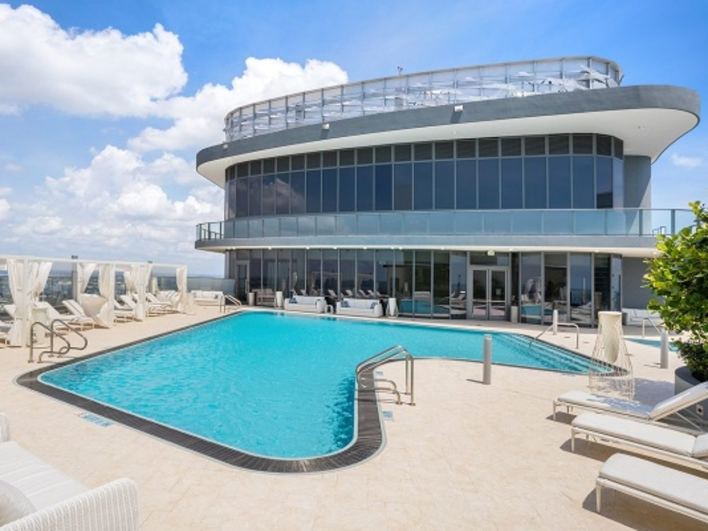 Exterior view of Brickell Flatiron condominiums outdoor pool with oceanfront view. Has lounge chairs and building.