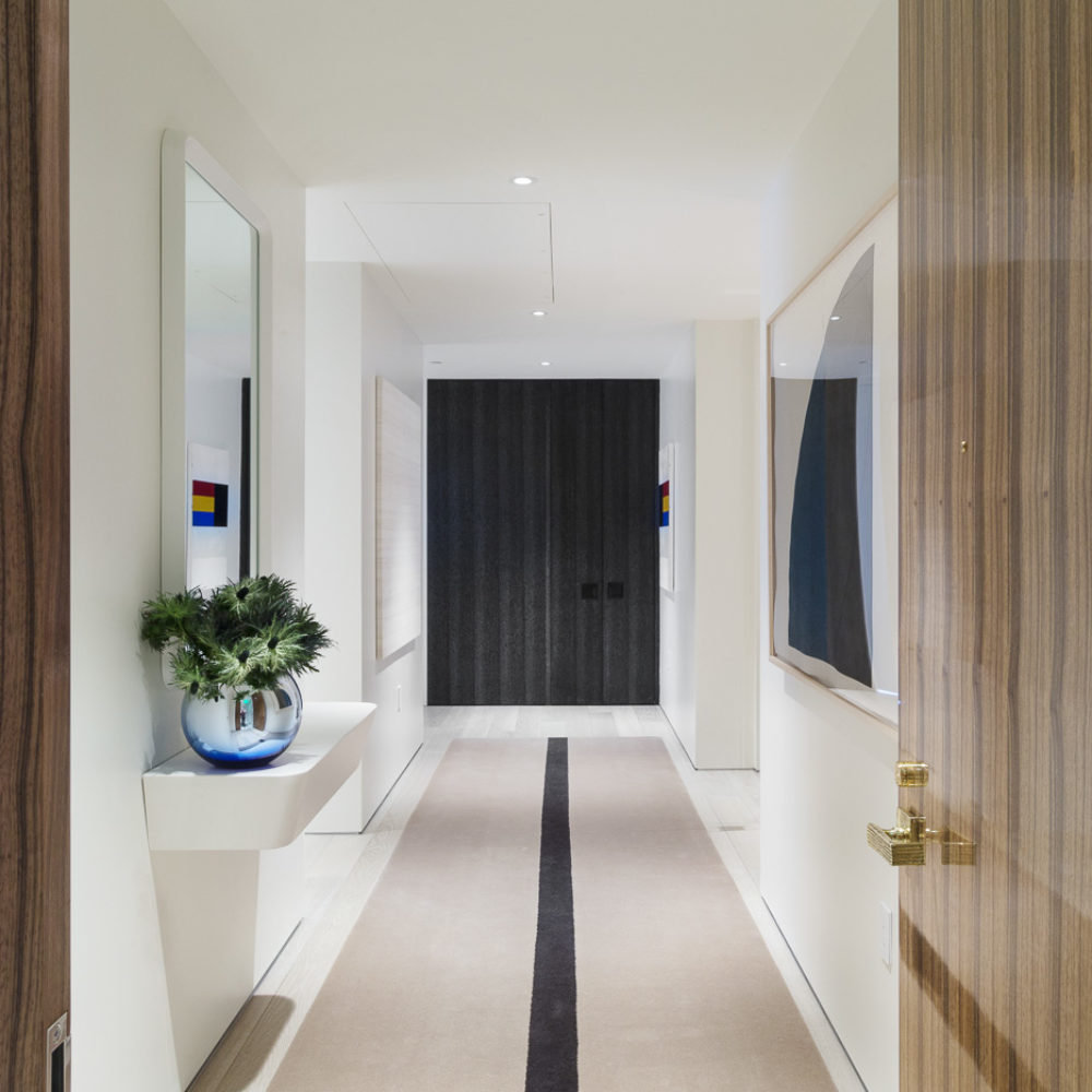 Interior view of residential hallway inside 181 Fremont located San Francisco. Includes white walls and tile flooring.
