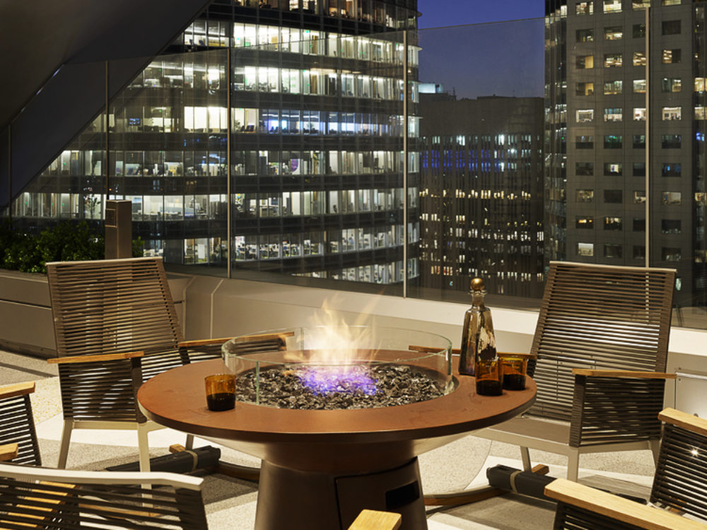 View of firepit located at the top of 181 Fremont condominiums with a view of San Francisco during the night.