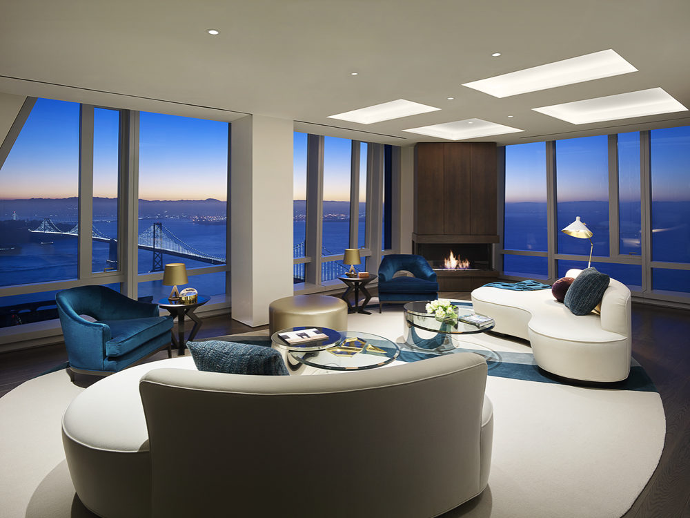 Interior view of 181 Fremont residence living room with skyline view of San Francisco. Includes couches and chairs to sit.