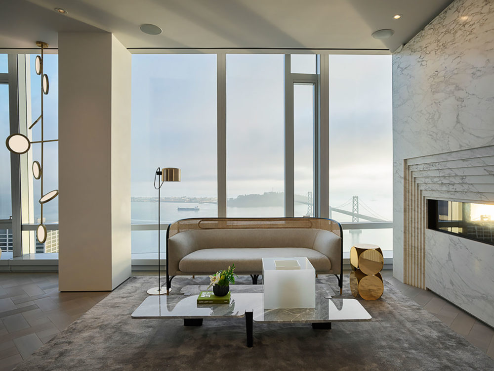 Interior view of penthouse residences in 181 Fremont with window view of San Francisco. Includes a coffee table and fireplace.