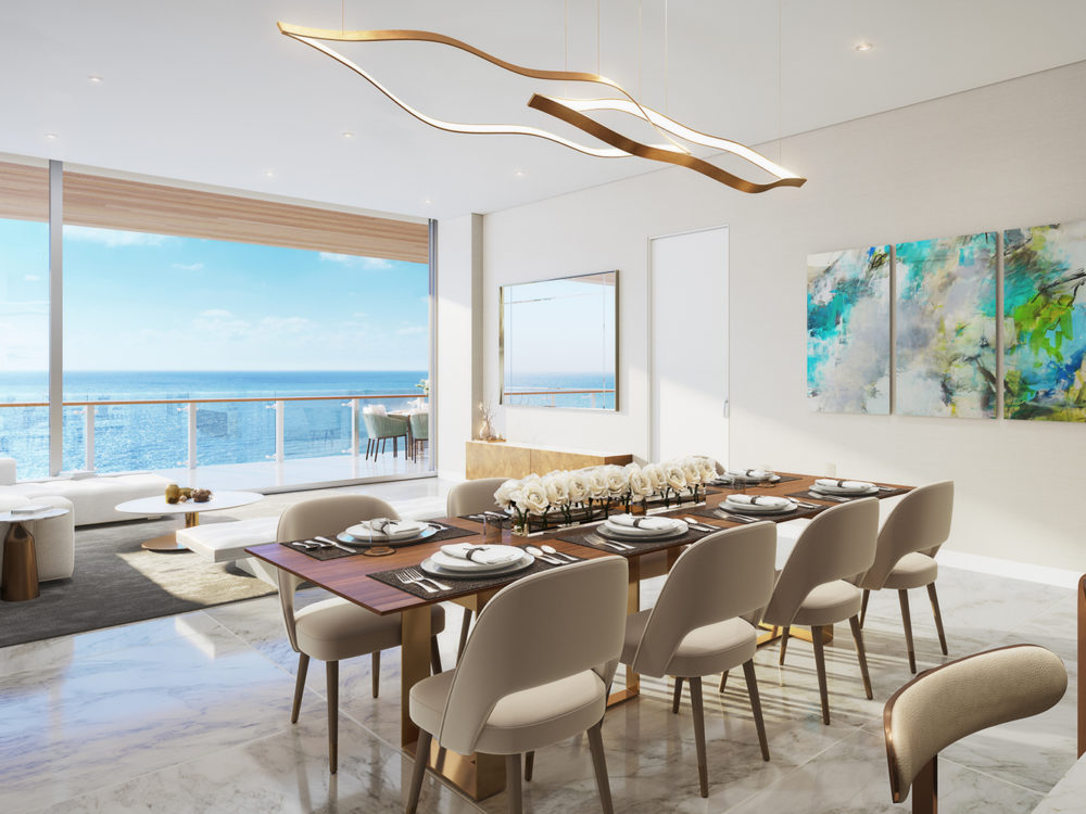 Interior view of 57 Ocean residence dining room with window view of Miami. Has view of kitchen countertop and dining set.